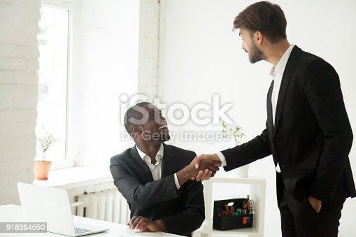 918364538 istock photo Grateful caucasian executive handshaking african employee congratulating with job promotion 918364550