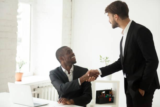 tacksam kaukasiska executive handskakning afrikanska anställd gratulera jobb marknadsföring - new job bildbanksfoton och bilder
