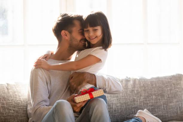 dankbare papa umarmte tochter für geschenk am vätertag - geburtstagsgeschenk für papa stock-fotos und bilder