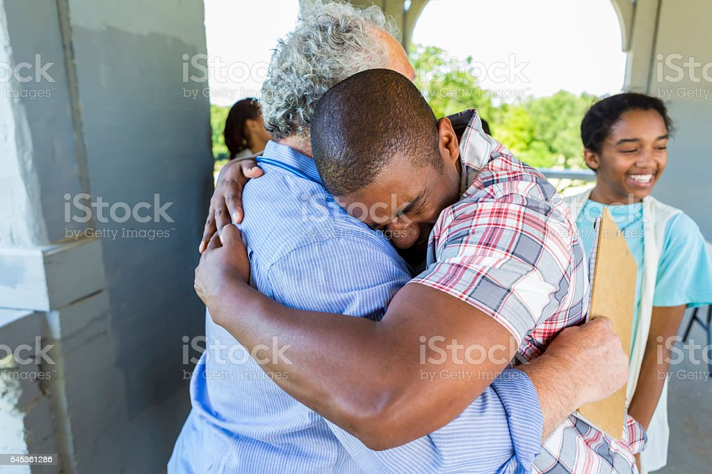 Grateful father embracing senior man stock photo