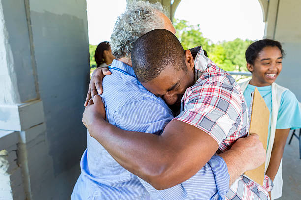 Grateful father embracing senior man Emotional African American father embracing the caucasian senior man in a light blue shirt. His daughter is standing smiling behind them, she is wearing a light blue shirt with a vest on top of it. relief emotion stock pictures, royalty-free photos & images