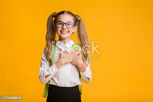 516544386 istock photo Grateful school girl smiling putting hands on chest, studio shot 1174446410