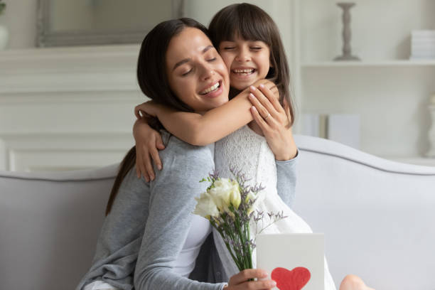 Grateful young mother embracing little cute daughter. Grateful young mother embracing cuddling hugging little cute daughter, thanking for birthday greeting card and flowers. Happy laughing family of two celebrating international women day or 8th March. birthday wishes for daughter stock pictures, royalty-free photos & images