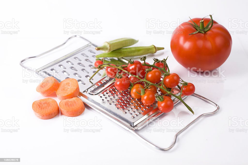 Grater and vegetables against a white background stock photo
