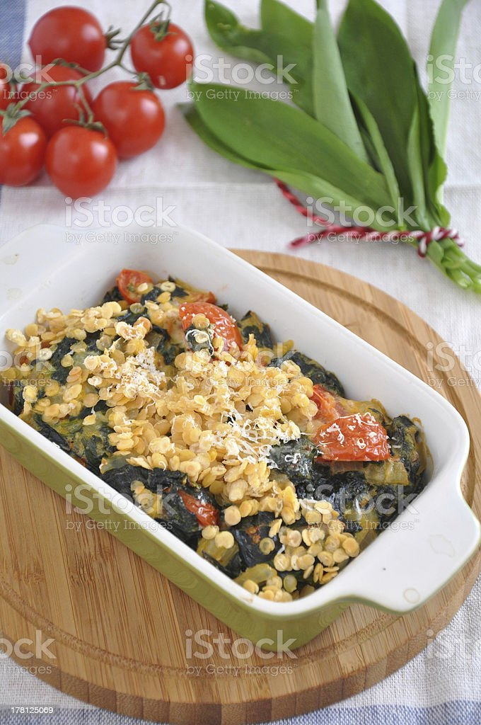 Gratin with spinach, red lentils and wild garlic royalty-free stock photo