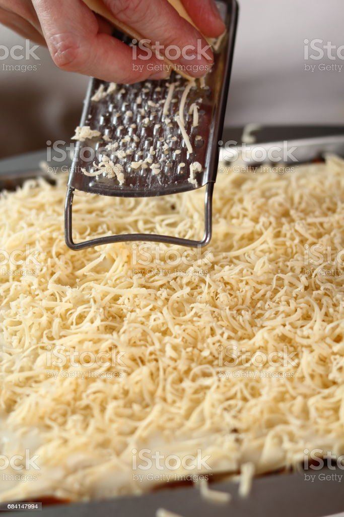 Grating cheese on top layer. Making Lasagna Bolognese Series. foto stock royalty-free