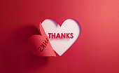 Thanks text is inside of a red folding heart shape on white background. Horizontal composition with  copy space. Gratitude concept.