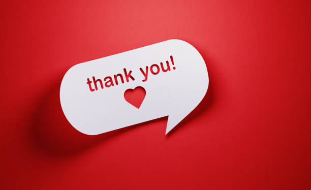 gratitude concept - white chat bubble  over red background - thank you стоковые фото и изображения