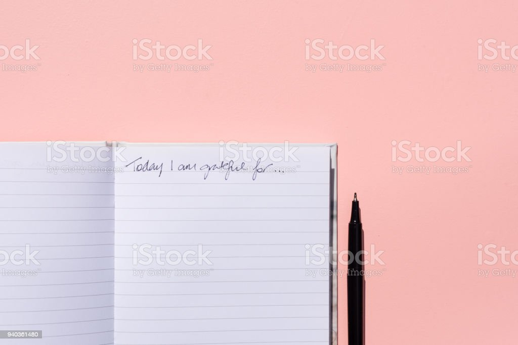 Gratitude journal and pen on pink background from above stock photo