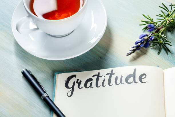 Gratitude journal with a pen, a cup of tea, and a flower stock photo