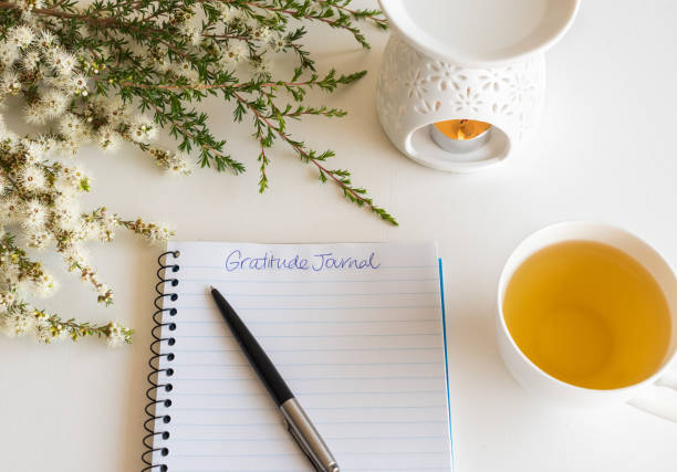 Gratitude journal with pen, cup and flowers stock photo