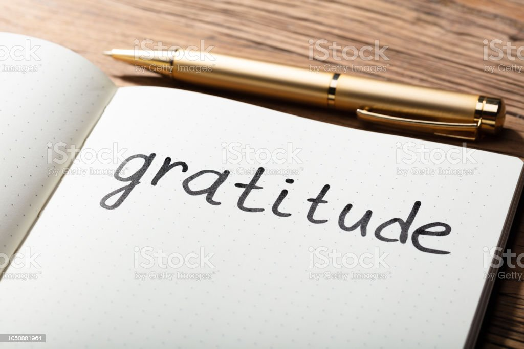 Gratitude Word With Pen On Notebook Close-up Of Gratitude Word With Pen On Notebook Over Wooden Desk Admiration Stock Photo