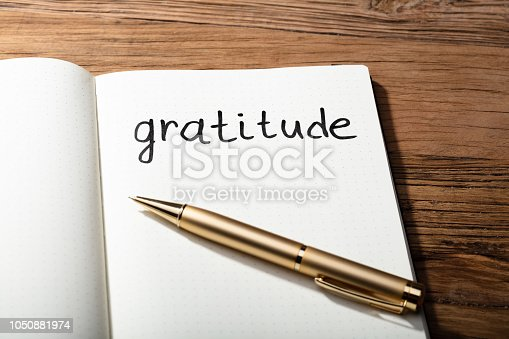 1050881964 istock photo Gratitude Word With Pen On Notebook 1050881974
