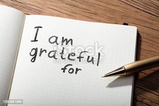 1050881964 istock photo Gratitude Word With Pen On Notebook 1050881980
