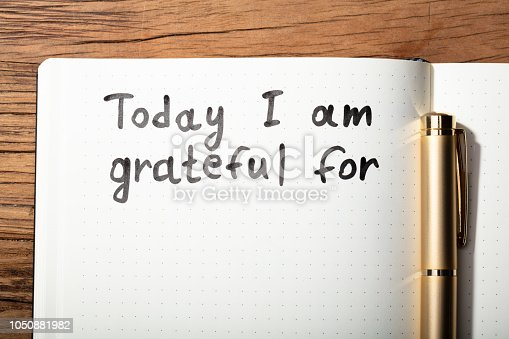 1050881964 istock photo Gratitude Word With Pen On Notebook 1050881982