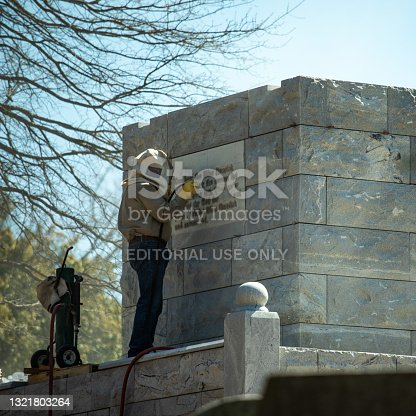 Atlanta, United States - March 2020: Man with safety equipment engraving a plaque at the cemetery
