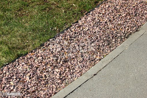 Gravel belt between lawn and sidewalk in a park