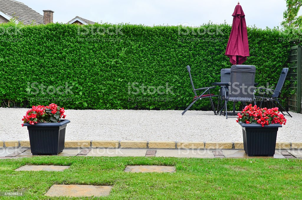 Gravel patio area with table chairs and parasol. stock photo