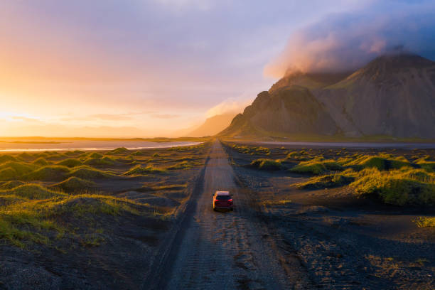 Gravel road at sunset with Vestrahorn mountain and a car driving, Iceland stock photo