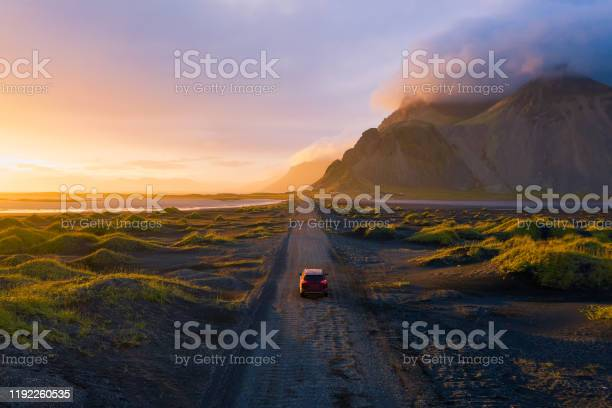 Photo of Gravel road at sunset with Vestrahorn mountain and a car driving, Iceland