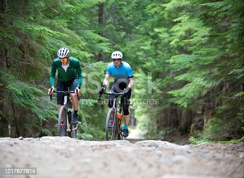 Two men go for a backcountry bicycle ride with their gravel road bikes on a forestry road in British Columbia, Canada. Their bikes are similar to cyclo-cross bikes with disc brakes and oversized tires suited for the rough terrain.