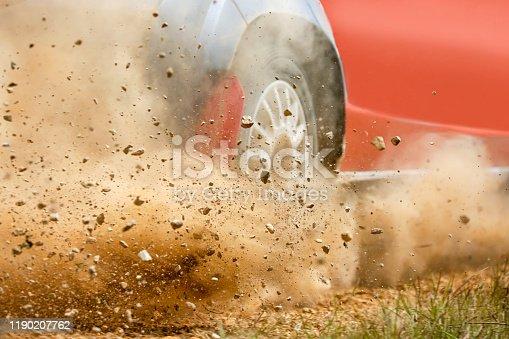 Gravel splashing from rally race car drift on track.