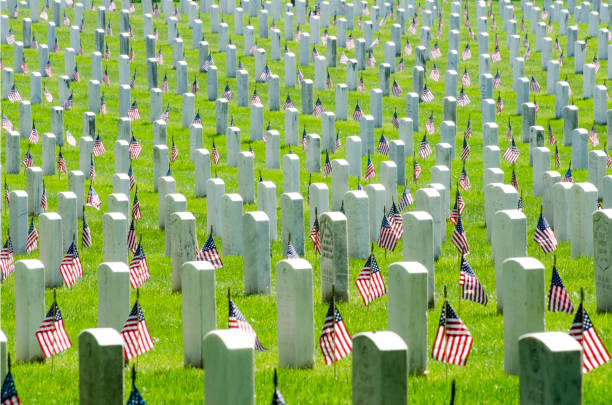 graves are marked with u.s. flags at arlington national cemetery - arlington national cemetery stock pictures, royalty-free photos & images