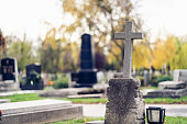 Graves at a cemetery. Cross in the foreground.
