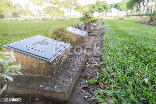 Graves in graveyard with beautiful green garden.