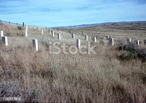 Vintage, authentic archival photograph of long rows of gravestones in a meadow in a rural area outdoors in Wyoming, United States, 1976