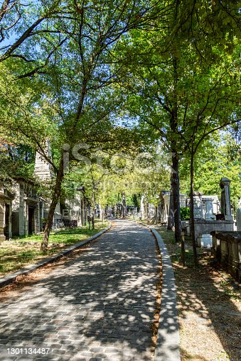 Paris, France - September 11 2019: Alley with Graves in Pere Lachaise Cemetery on a sunny day of september.