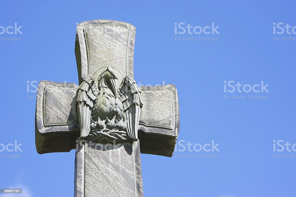 Gravestone Cross with Carving of Eagle feeding Chicks in Nest royalty-free stock photo