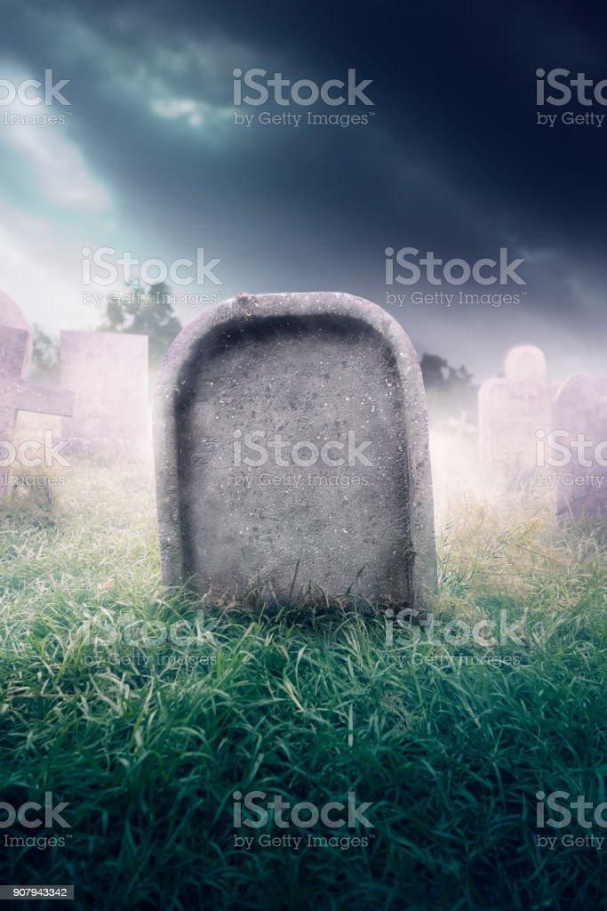 gravestone with fog and dramatic lighting stock photo