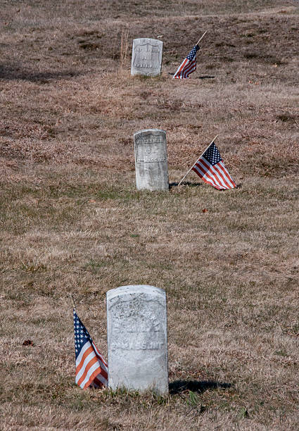 Gravestones anf Flags Honor Veterans Weymouth, MA, USA-March 9, 2016: Three old granite gravestones with American flags next to each of them are arranged front to back in a grassy field. These grave markers each honor a military veteran who fought in the Civil War. civil war memorial minnesota stock pictures, royalty-free photos & images