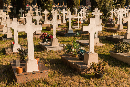 Gravestones crosses and gifted flowers in San Michele Cemetery, Venice, Italy