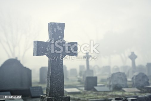 A cemetery on a rainy day with various crosses and headstones.