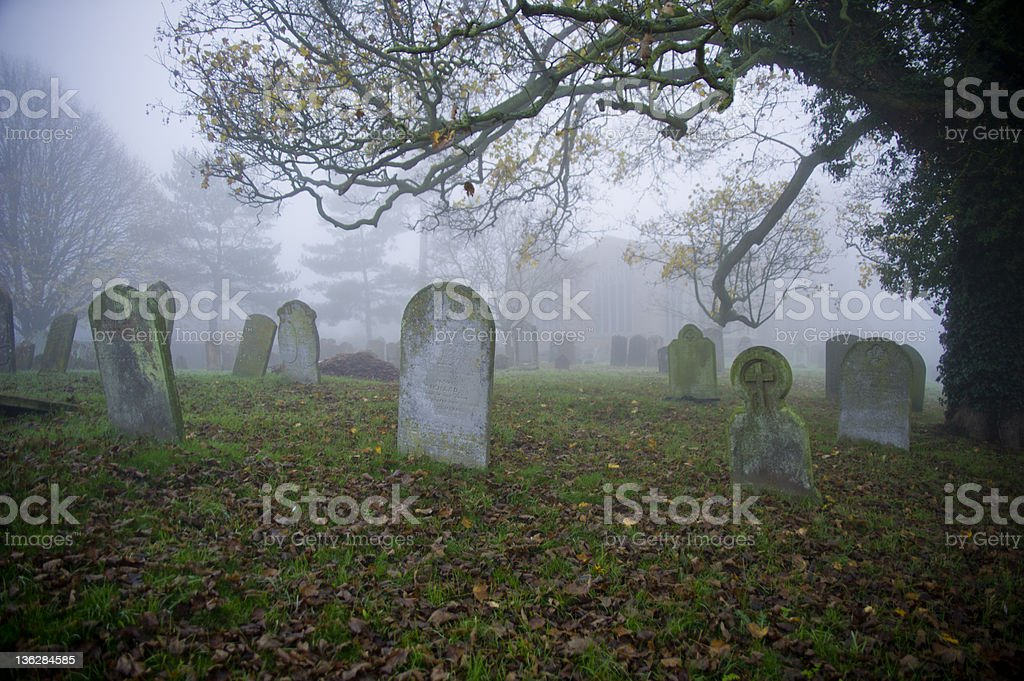 Graveyard with tombstones and fog Tombstones in a graveyard, all names on tombstones over two hundred years old. Cemetery Stock Photo