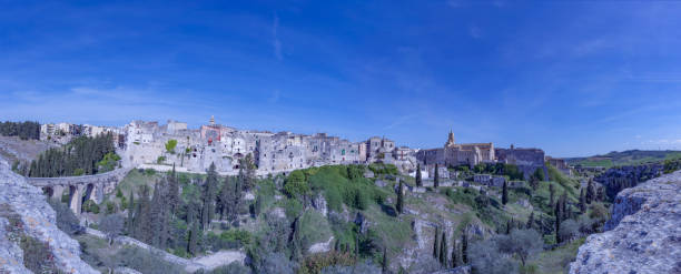 Gravina di Puglia, panorama. View of houses overlooking the canion. Old Town. Gravina di Puglia, panorama. View from the edge of the truck. Church, bell tower and dome. mattock stock pictures, royalty-free photos & images