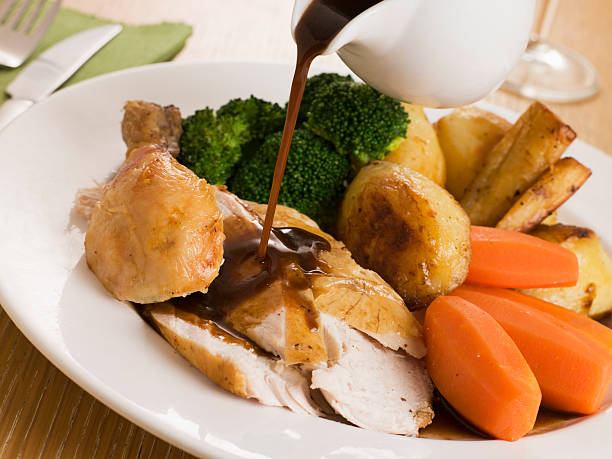gravy being poured over a plate of roast chicken - gebraden vlees stockfoto's en -beelden