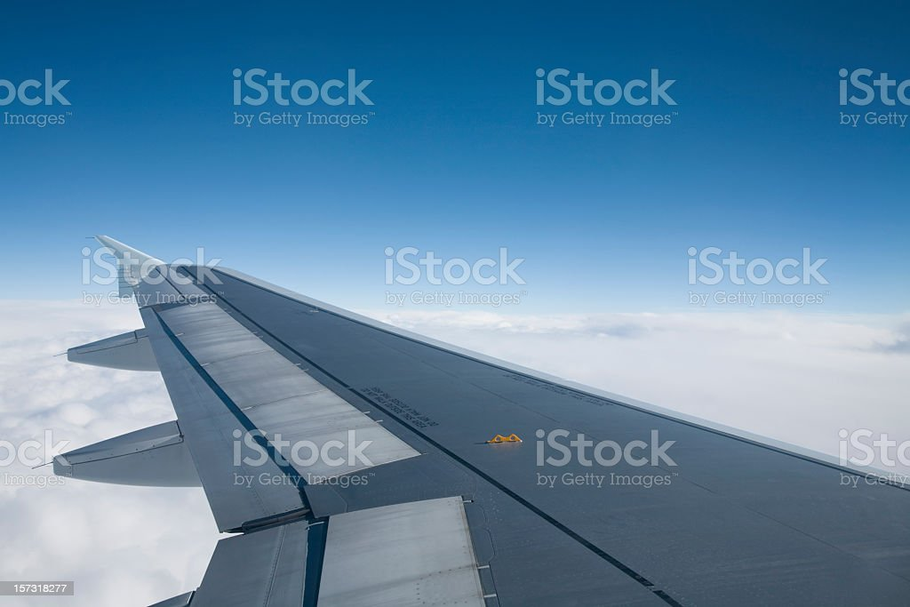 A gray airplane wing against a cloudy blue sky royalty-free stock photo
