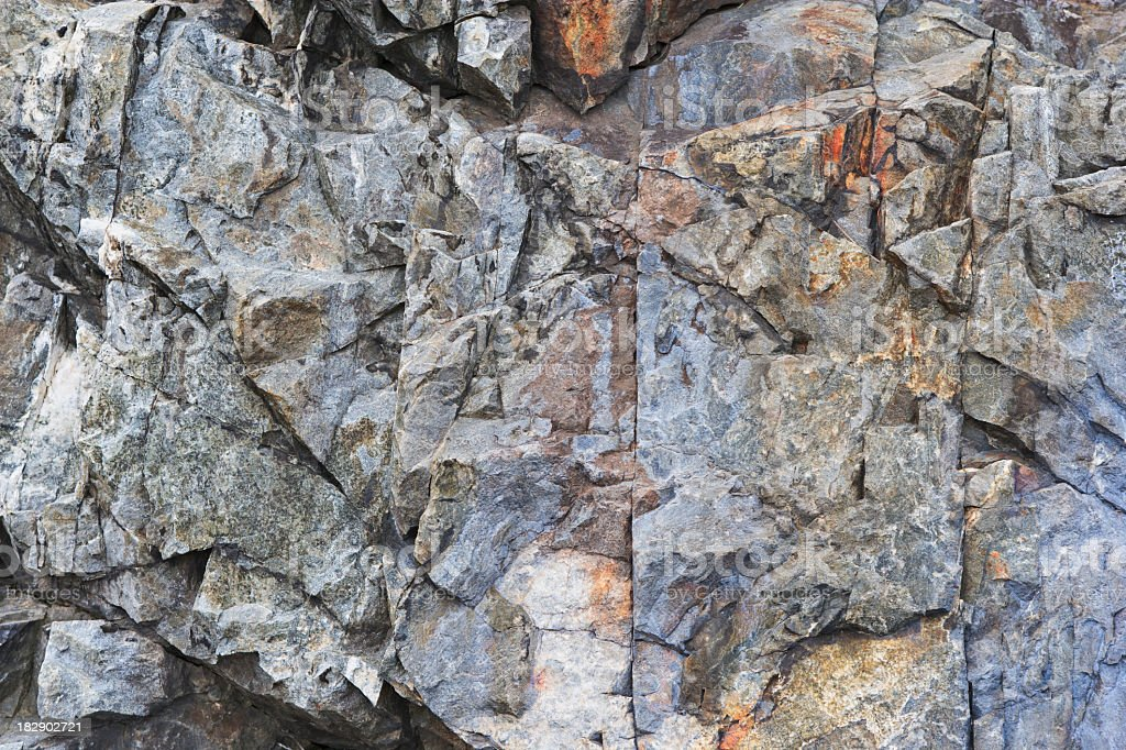 Gray and orange jagged rocky cliff  stock photo