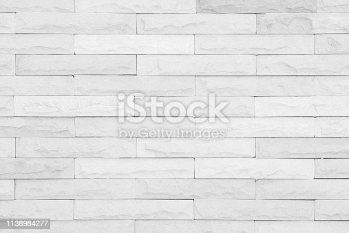 Gray and white brick wall texture background. Brickwork or stonework flooring interior rock old pattern clean concrete grid uneven bricks design stack.