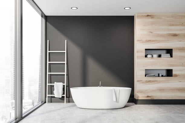 Gray and wooden bathroom with tub and ladder stock photo