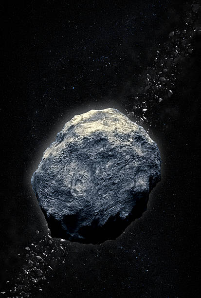 A gray asteroid heading for earth against a dark background stock photo