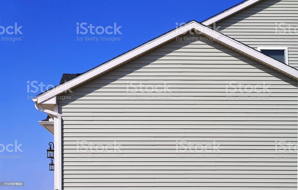 Gray back of home with slats and vinyl white gutters royalty-free stock photo