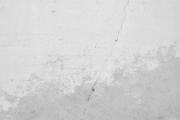Grauer Hintergrund einer Betonwand mit einem Riss Quer durch das Bild. Mittelgrauer Verlauf und verputzte Stellen im unteren Bild. Texturierte Wand im Industrie Style. – Foto