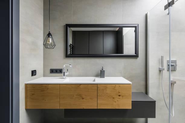 graue badezimmer mit arbeitsplatte waschbecken - badezimmermöbel holz stock-fotos und bilder