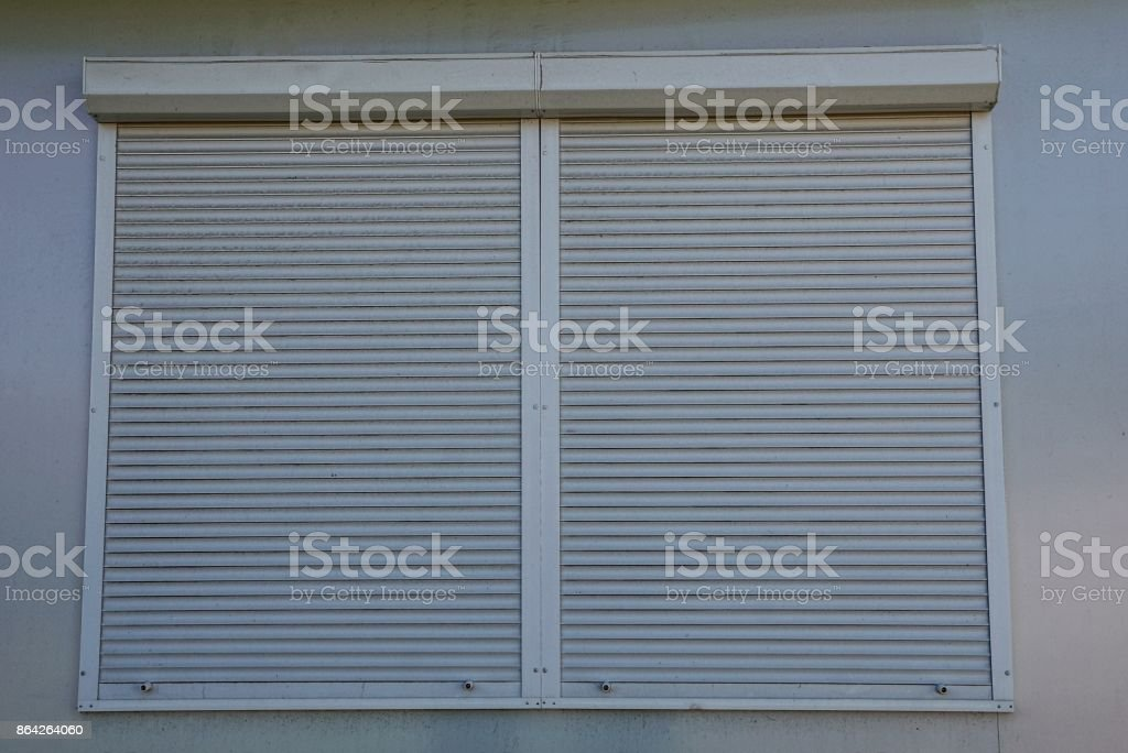Gray blinds on a closed window on the wall of the building royalty-free stock photo