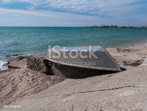 Gray boat on an empty sand beach. Cloudy sky vivid blue water. Fishing concept. Marine wallpaper copy space. Ship on a beach on a sunny day. Travel lifestyle photo.