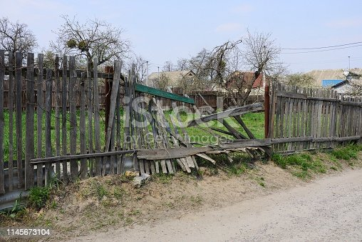 old gray broken wooden plank fence in green grass on a rural street